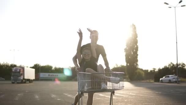 Šťastný mladý pár s nákupním košíku na parkovišti u supermarketu. Lidé nosí ležérní oblečení a brýle. Muž a žena líbala s zábava venku
