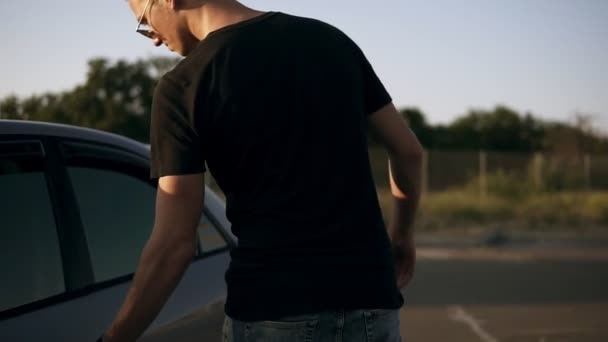 Young attractive man in black T shirt and sunglasses get in car, dark silver sedan and ready to go with her girlfriend from the parking lot