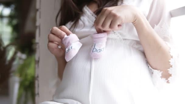 Těhotná, krásná žena, sedící na parapet u okna. Držení Baby botičky, takže malé kroky na její těhotné břicho. Uvnitř