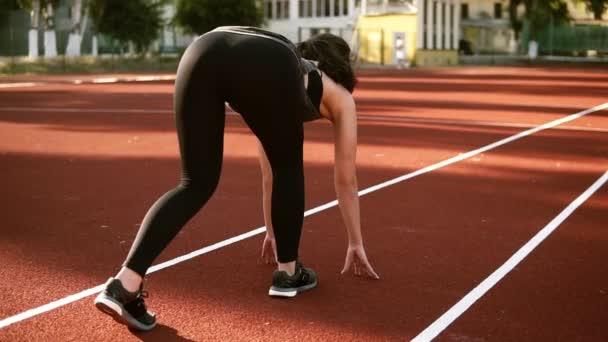 Atlet žena začíná běh na běžecké dráze. Sportovní bruneta žena v černém legíny zaběhat trackline na venkovní stadion. Zadní pohled
