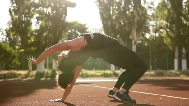 Fit woman doing bridge pose yoga exercise from sitting position. Brunette caucasian woman exercising muscles, training flexibility. Outdoors stadium