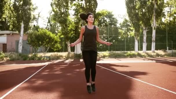 Sportliche Brinette Mädchen Turnen mit einem Springseil Springen hoch, scrollt das Seil mehrmals. Natur-Stadion. Vorderansicht