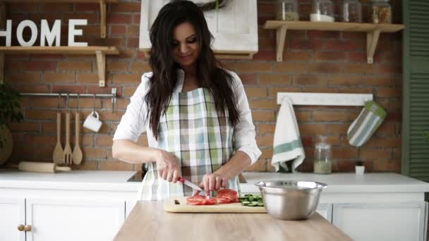 A beautiful pregnant girl in a white shirt and plaid apron cuts vegetables, prepares a salad in her modern, decorated kitchen. Front footage view