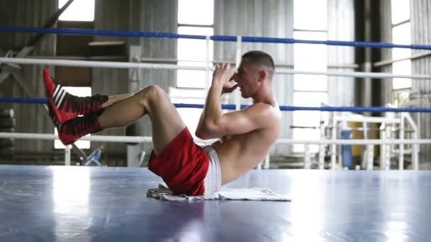 Muž je cvičení v tělocvičně. Ležet na zádech a zvedá se hrudník s nohama nahoru, břišní tiskové cvičení. Boxerský ring, uvnitř