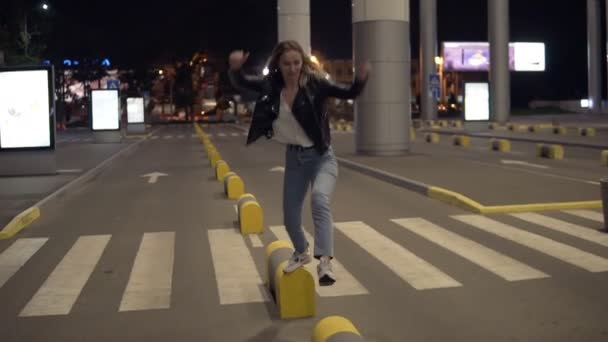 Mladá blond žena v džínách a černou koženou bundu, skákání na žlutý pouliční nárazníky v noci, baví. Street, bílé město světla, přechod pro chodce na pozadí. Pohled zepředu