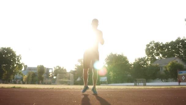 Plná délka sportovní muže v černé sportovní skákání, rozcvičení před tréninkem na stadionu venku. Koncept zdravého životního stylu, sportovní aktivity