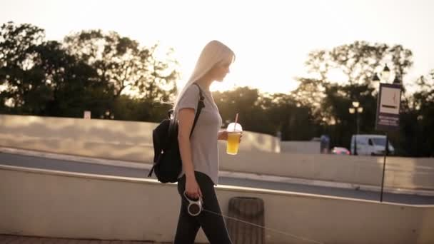 Side view of a blonde woman walking with a dog at the leash in the city. Walking in the park or street, holding an orange drink in plastic cup. Sun shines on the background