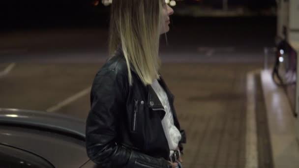 Palivo pro automobily. Atraktivní Kavkazský žena stojící vedle auta při tankování ho. Blondýnka, opíraje se o auto. Noční
