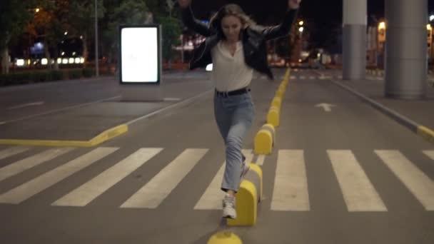 Mladá blond žena v džínách a černou koženou bundu, skákání na žlutý pouliční nárazníky v noci, baví. Street, bílé město světla, přechod pro chodce na pozadí