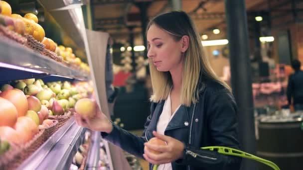 Prodej, jídlo, nakupování, konzumu a lidé koncept. Blond žena volba ovoce z barevné regály v supermarketu. Boční pohled