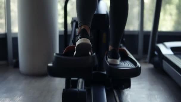 Hintergrundaufnahmen einer hinreißend athletischen jungen Frau, die in schwarzen Turnschuhen, Leggings und schwarzem Sport-BH im Fitnessstudio auf dem X-Trainer trainiert. Fitness, Abnehmkonzept