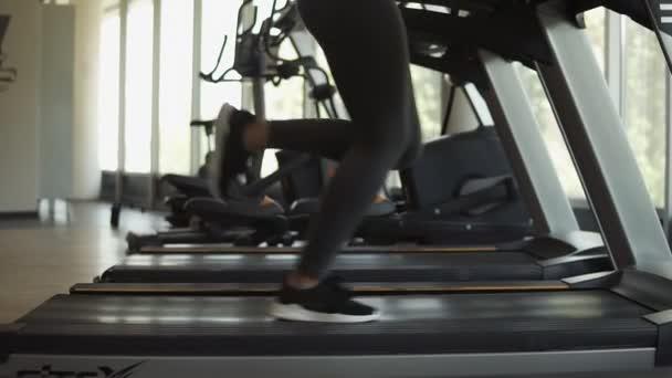 Attraktive junge sportliche Frau arbeitet im Fitness-Studio heraus. Cardio-Training auf Laufband zu tun. Läuft auf Laufband. Seitenansicht