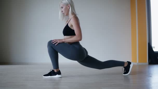 Čelní pohled sportive blondýna v černé podprsence a šedé leginy strečink nohou dělá jógu asana v posilovně klubu epmty