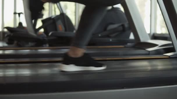 Detailní záběry Zenske nohy v snakers běh na běžícím pásu ve fitness klubu. Blond žena v šedé leginy a sportovní podprsenka cvičit v tělocvičně
