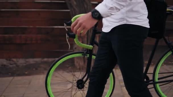 K nepoznání zamyšlený mladý podnikatel chůzi s kolo na ulici ve městě. Válcování jeho trekingové kolo při chůzi