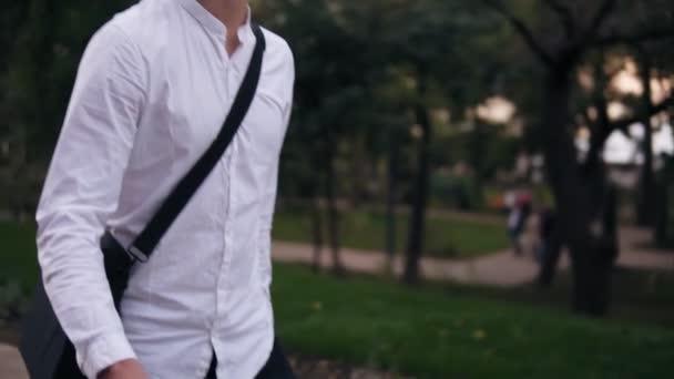 Kavkazská mladý podnikatel chůzi s kolo na ulici ve městě. Válcování jeho trekingové kolo při procházce parkem s notebookem na rameni. Zpomalený pohyb