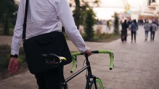 K nepoznání zamyšlený mladý podnikatel chůzi s kolo na ulici ve městě. Válcování jeho trekingové kolo na procházce v parku crowdy