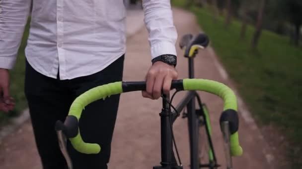 K nepoznání zamyšlený mladý podnikatel chůzi s kolo na ulici ve městě. Válcování jeho trekingové kolo při chůzi. Pohled zepředu