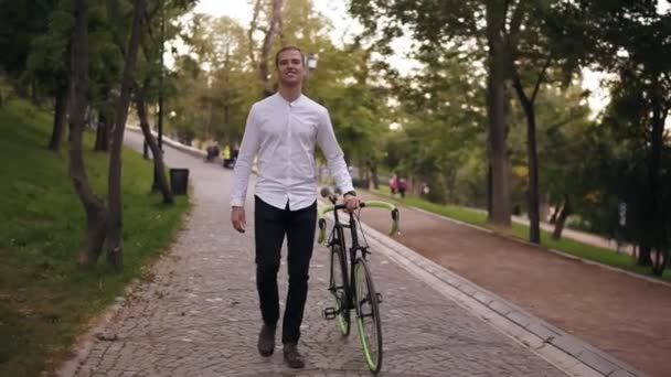 Full length of caucasian smiling young man in white shirt walking with bicycle on the street in town. Rolling his trekking bike while walking by park. Front view