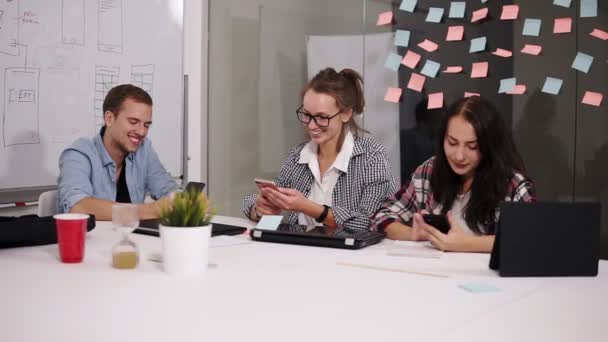 Group of three young coworkers sitting in the modern loft office white huge table, looking at their smartphones, discussing something. Positive business people during the teamwork