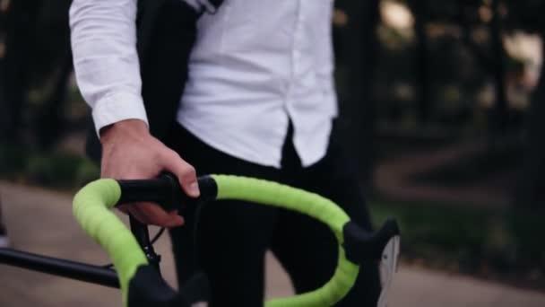 Zamyšlený mladý podnikatel chůzi s kolo na ulici ve městě. Válcování jeho trekingové kolo při procházce parkem