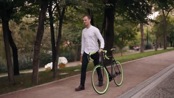Po celé délce kavkazské usmívající se mladý muž v bílé košili chůzi s kolo na ulici ve městě. Válcování jeho trekingové kolo při procházce parkem. Boční pohled
