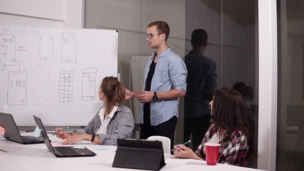 Mladý muž v brýlích, sdílet své názory s kolegy v zasedací místnosti během obchodního jednání. Tým odborníků s nové projektové setkání v zasedačce