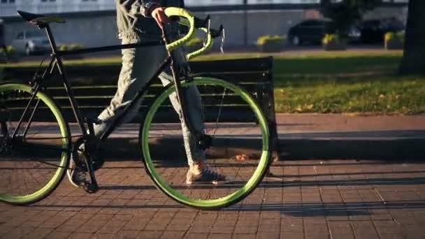 Zblízka záběry ženy v teniskách chůzi vedle na kole ráno parku nebo na ulici. Boční pohled na mladé ženy chodit s její trekingové kolo, v ruce drží suchý list