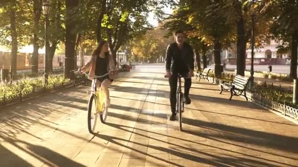 Front view of a young couple or friends riding their bikes in the city park or boulevard in summertime. People, leisure and lifestyle concept