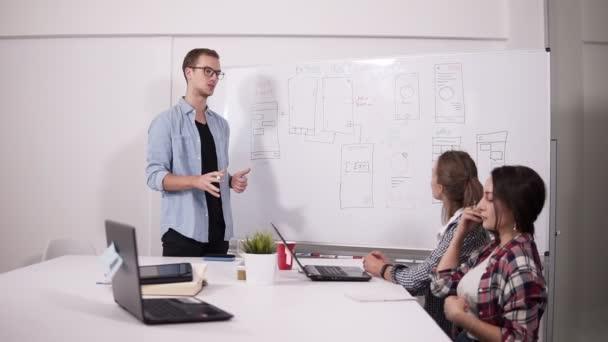 Partner, die zusammenarbeiten, Finanzberichte analysieren, effektive Geschäftslösungen während eines Unternehmenstreffens finden. zwei Frauen am Schreibtisch und ein Mann bei der Präsentation neben den Arbeitsblättern