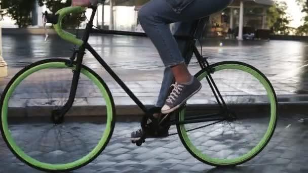 Zblízka záběry ženské nohy, jízda na kole na kole ráno v dlážděné ulici s mokré asphslt. Boční pohled na mladá žena na koni trekingové kolo s zelenou koly, nosí tenisky a džíny