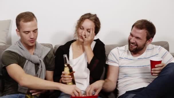 Barátság, a kommunikáció, a buli - vidám kaukázusi meg beszél, szórakozás, beltéri fotelben ülve és nevetve, pattogatott kukorica, evés ivás. Férfi és női társaság. Közelről