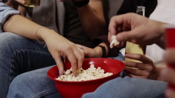 Közelről egy piros tál pattogatott kukoricát és egy üveg sör vagy szódás a lábak. Kézzel megragadja a popcorn a tálból. Barátság, film, buli