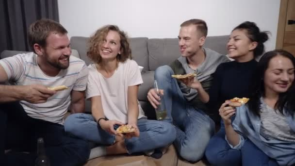 Friendship, food, domestic party time - cheerful caucasian friends order pizza, having fun, sitting on floor indoors and laughing, eating, drinking. Front view