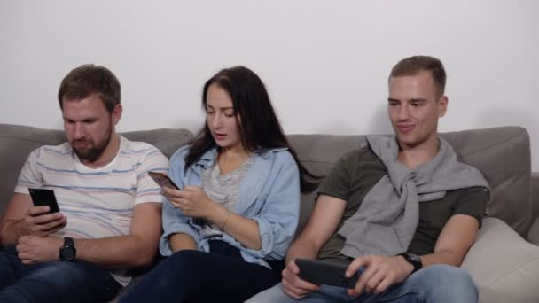 Diverse young people sitting in row on couch together obsessed with devices online, caucasian addicts using their smartphones, digital life and gadgets overuse concept