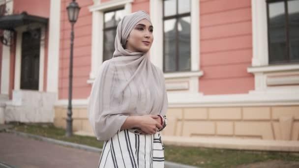 selbstbewusste und attraktive Frau im Hidschab. junge Frau geht schräg durch die Stadtstraße mit einem schönen rosa und beigen Gebäude im Hintergrund