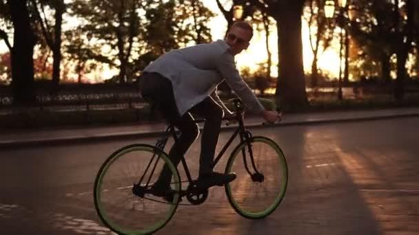 Šťastný mladý muž jedoucí na kole na silnici prázdné kolo Zelený strom parkem na letní slunečný den ráno
