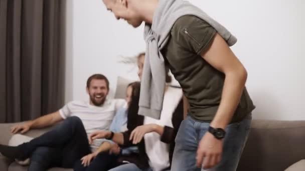 Barátság, kommunikáció, buli - vidám kaukázusi meg együtt szórakoztunk, miközben egy szürke kanapén bent ültünk, és nevetve átfogó