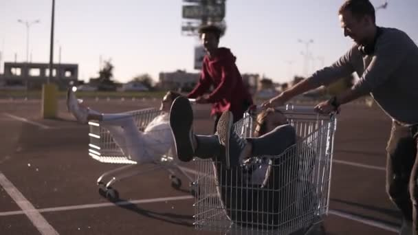 Young friends having fun on a shopping trolley. Multiethnic young people racing on shopping carts on the parking zone. Couple having time together on summer