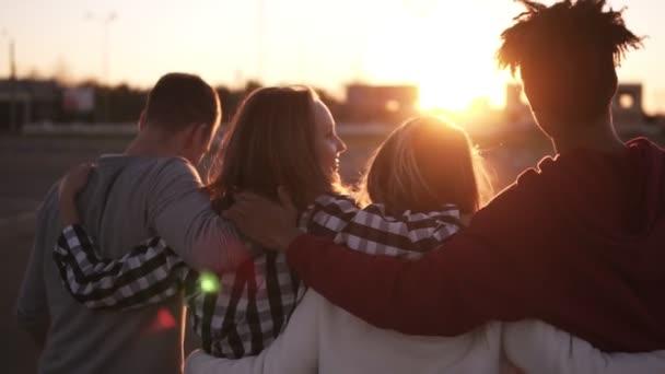 Gruppo di amici che camminano abbracciando e divertirsi insieme in città. Sono due ragazze e due ragazzi ventenni, amicizia e concetti lifestyle, abbigliamento autunno. Sole fortemente la
