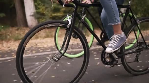 Couple riding bikes along the asphalt road in local park early in the morning in autumn day. Close up of legs pedaling and wheels . Side view