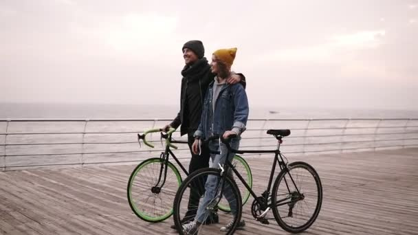 Beautiful smiling couple of young hipsters walking together embracing with their bikes near the sea at autumn day. Young girl in yellow hat pointing on something. Walking by wooden deck in daytime