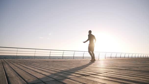 Motivované mladého sportovce vykonávajících skákání přes švihadlo na pobřeží. Mladý muž věnuje boxu cvičit venku. Zpomalený pohyb. Východ slunce. Steadicam