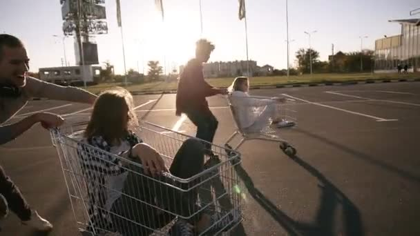 Happy laughing multirace couples enjoys shopping trolleys dancing or battle with trolley in the supermarket parking zone. Evening dusk