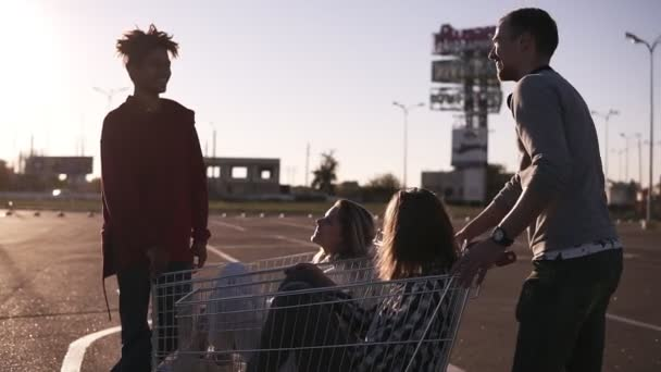 Young friends having fun on a shopping carts. Multiethnic young people playing with shopping cart. Malefriends standing near the shopping corts with their girlfriends. Outdoors