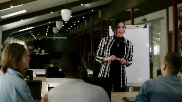 Diverse business people at seminar sitting in a modern office. Young millennial leader female standing near whiteboard talking to young colleagues clients at business meeting