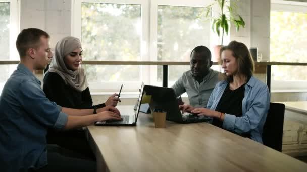 Különböző emberek használ laptop ülve előtt világos munkahelyen az ablak, több-etnikumú és a multi kulturális fiatalok dolgozó csapat, indítás megvitatását