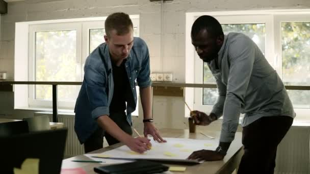 Two business partners are working together, brainstorming, pointing at the table with yellow papers on it with the pencils on business meeting. Mixed raced collegues planning or discussing the problem
