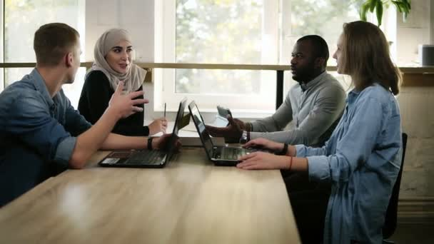 Group of four young mixed race and cultural people - muslim woman, african man and two caucasians have a meeting together, sitting at the table with open laptops and have disscussion, talking about