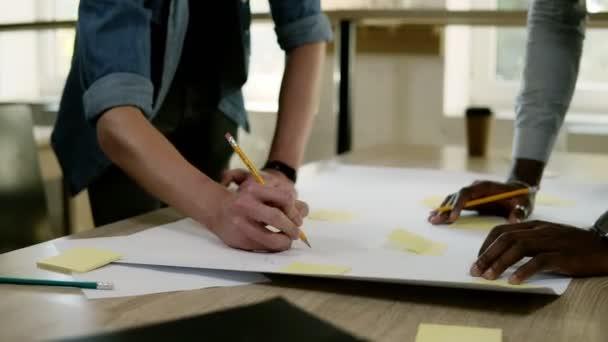 Dva smíšené audiosystém obchodní partneři jsou společně, brainstorming, směřující ke stolu s žluté papíry na ní s tužky a dělala si poznámky. na obchodní jednání. Partneři, plánování nebo